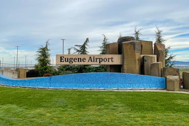 The sign and artwork of a blue tile river, real basalt columns and evergreen trees welcoming visitors to the Eugene Airport.