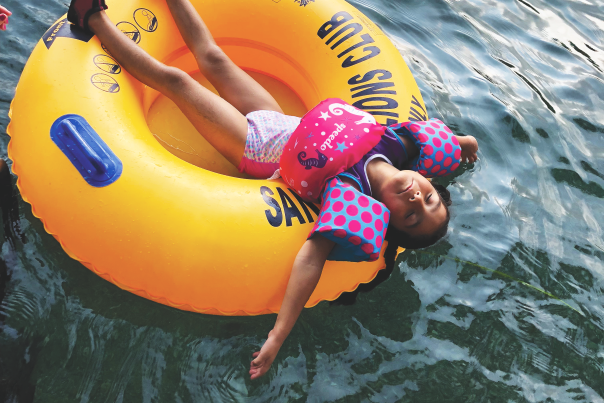 Little girl relaxing in a yellow tube on the San Marcos River.