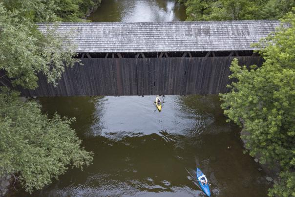 Two kayaks going under covered bridge in Kent County.