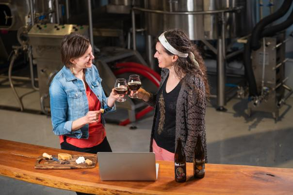 Two women standing in front of a laptop toast glasses of beer