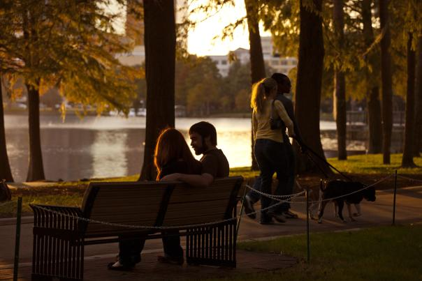 A couple sitting on a park bench and another couple walking their dog along Lake Eola