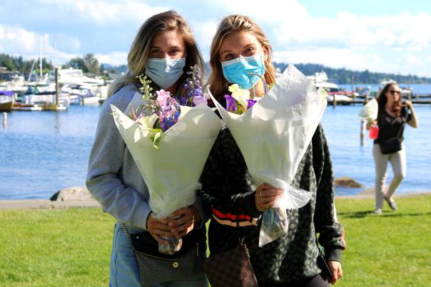 Two young ladies wearing facemasks holding flowers at Marina Park