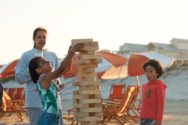 A young girl and her family play giant Jenga on the beach in Port Aransas, TX