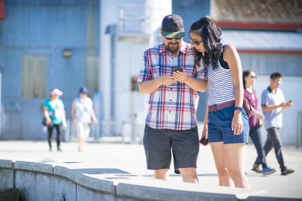 Two people check a clue on their phone.