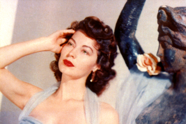Ava Gardner in a blue dress in front of a statue