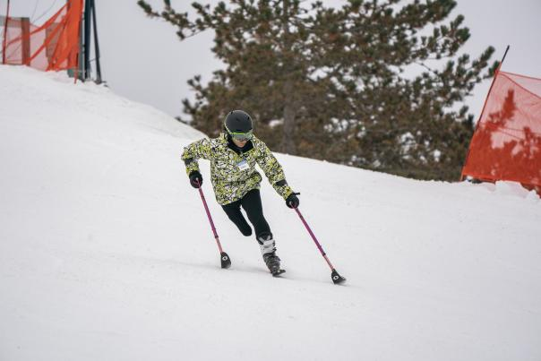 """Woman skiing downhill on one ski and two """"outriggers"""" - poles with skis on the bottom of them. http://wp.skiccsa.org/"""