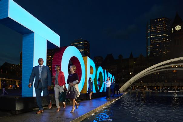 Convention delegates at the Toronto sign at  Nathan Philips Square