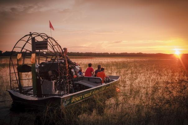 Guests on an airboat tour during sunset at Boggy Creek Airboat Adventures.