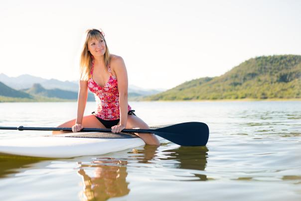Woman sitting on a paddle board in a Phoenix lake
