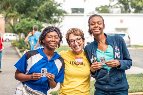 A volunteer posing with two young ladies who just received their ID courtesy of IDignity