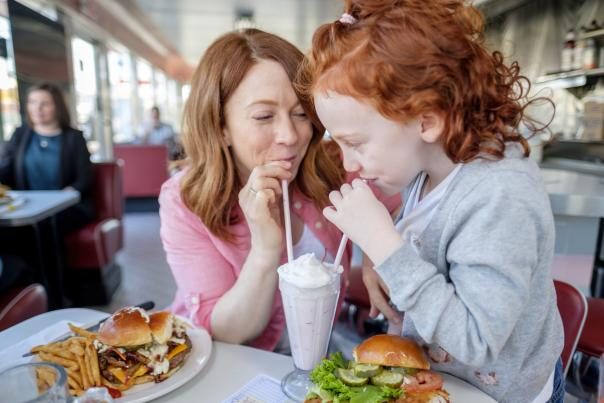 Oasis Diner mother and daughter sipping milkshake