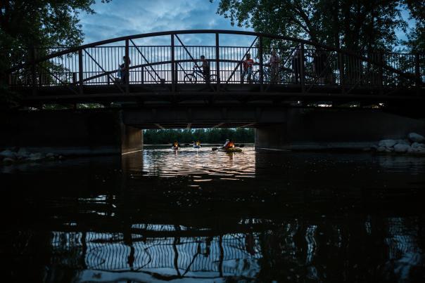 Paddlers enjoying kayaking at nighttime at Riverside Park.