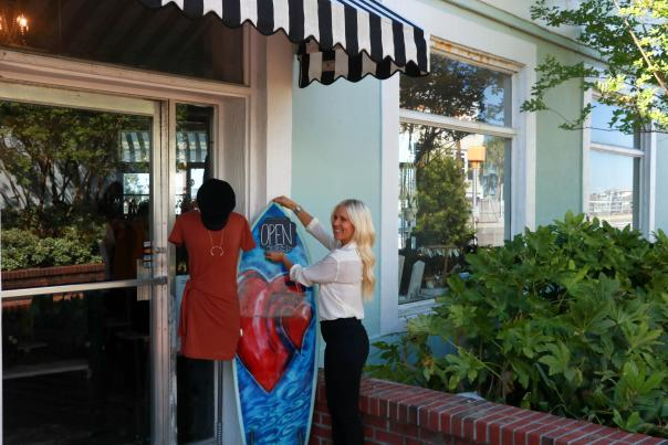 A woman hanging an Open for Business sign outside a shop in Wrightsville Beach, NC