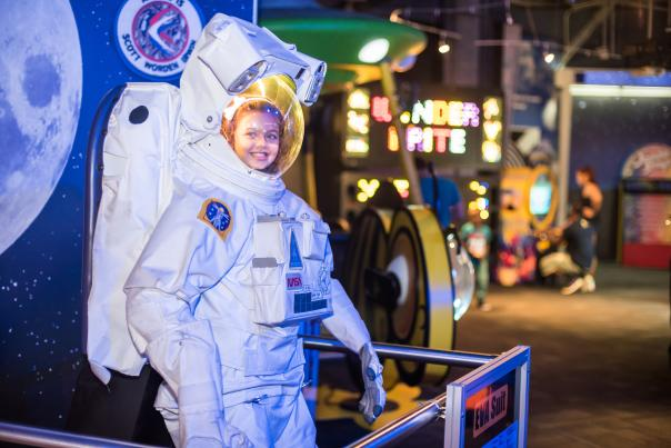 A girl tries on an astronaut suit at WonderWorks in Orlando.