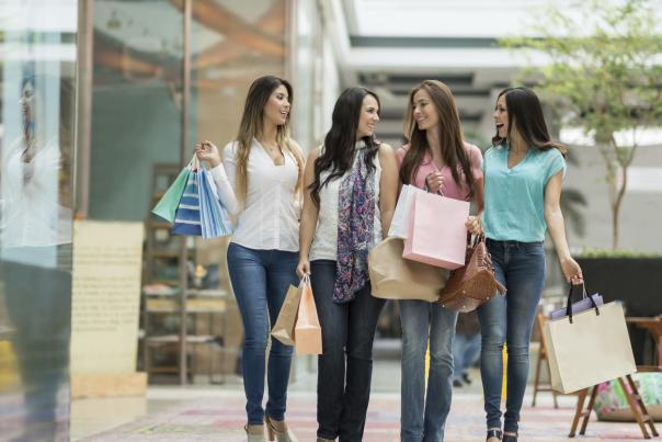 A group of four women holding their shopping bags as they walk together, side by side, at a shopping center.