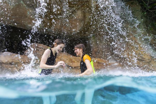 Two girls playing waist deep in the water underneath a waterfall at Discovery Cove