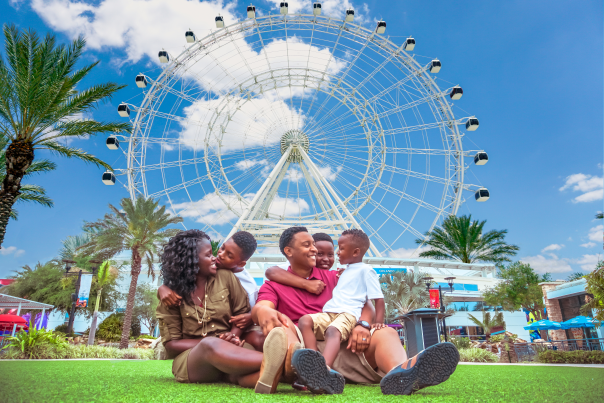 ICON Park family sitting on lawn in front of The Wheel