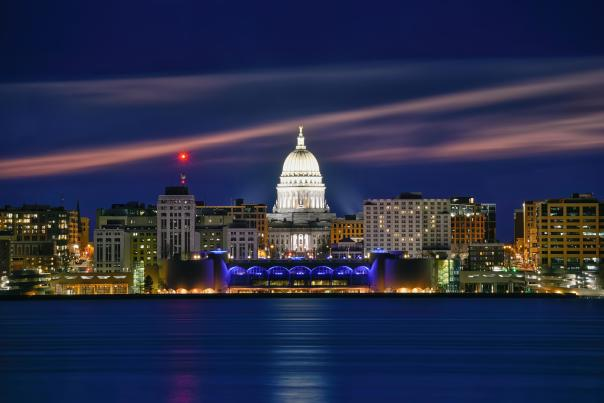 Night time view of downtown Madison from Lake Monona. The Capitol is lit up with bright white lights, and the Monona Terrace has blue lights along the arches. One of the buildings has lights on in a heart shape.