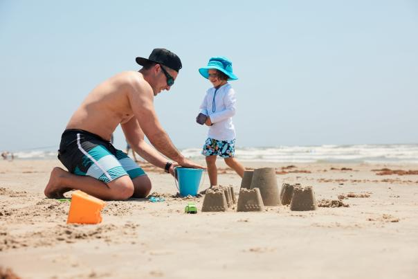 A man in a swimsuit kneels on the sand next to a child wearing sun gear and a hat. They pack sand in a blue bucket and build a sandcastle.