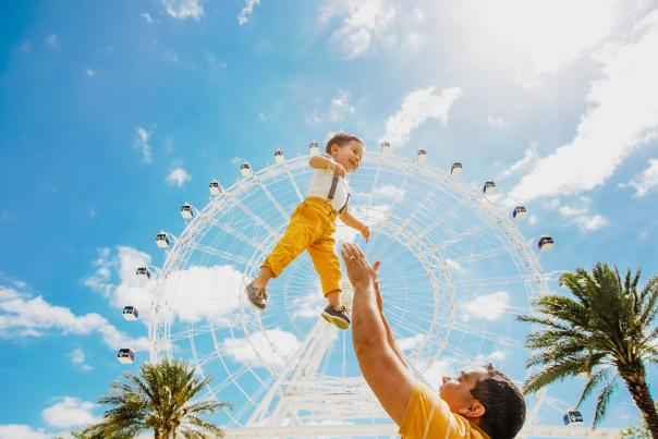 father throwing son up in air in front of The Wheel at ICON Park