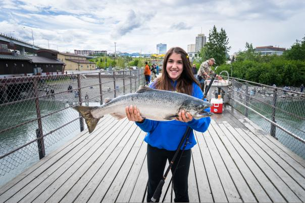 Girl holding a salmon at Ship Creek, Anchorage's urban fishery.