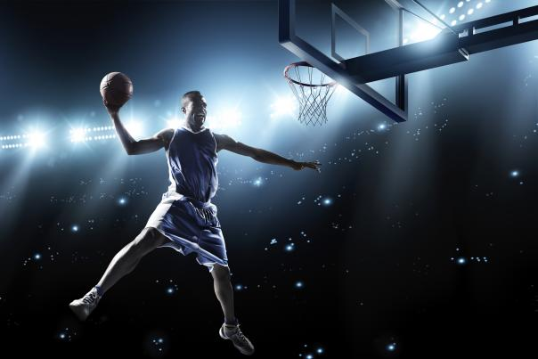 A male basketball player, in the air, ready to dunk the ball