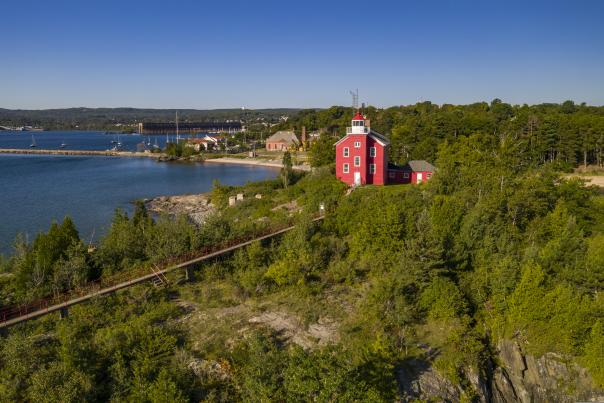 An aerial image of the Marquette Harbor Lighthouse on the rocky coast of Lake Superior.