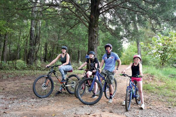 family on bikes in wooded trail