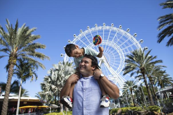 A boy sits on top of his dad's shoulders, while smiling and holding a lollipop, in front of The Wheel at ICON Park