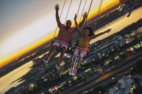 A couple riding the Orlando Starflyer high in the air at ICON Park