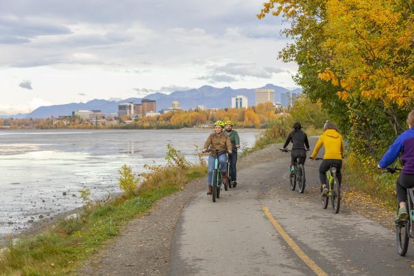 Couple biking the Tony Knowles Coastal Trail in the fall