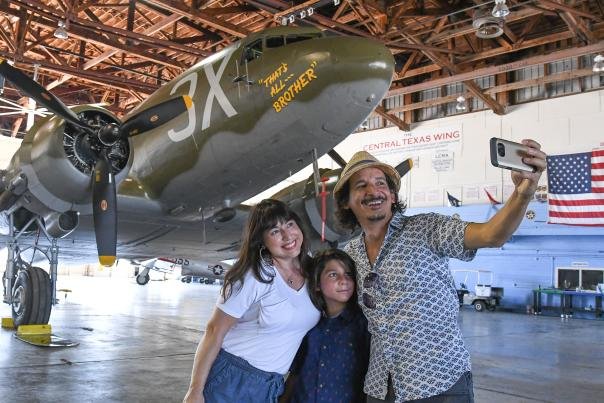 Family with little boy taking photo at WWII Bommer plane