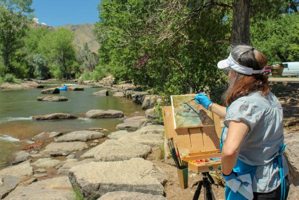 lady painting in front of clear creek