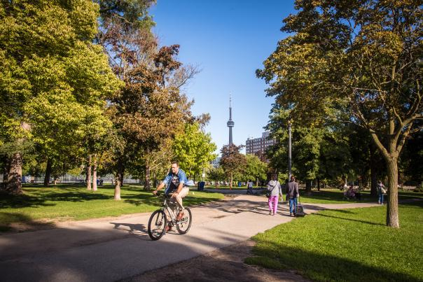 People ride their bikes through Trinity Bellwoods Park with a view of the CN Tower in the background