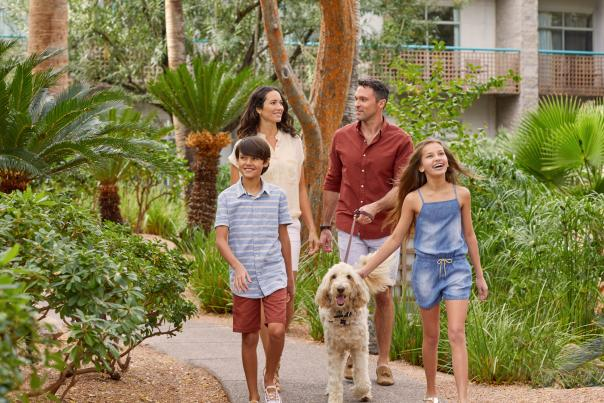 Family walking dog throughout resort walkways