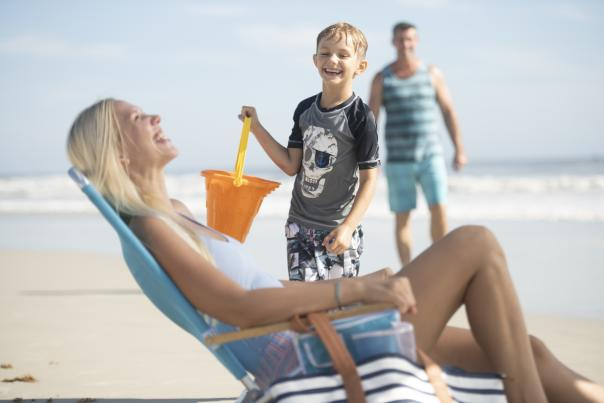 A mother enjoys the antics of her son during their beach day on Daytona Beach