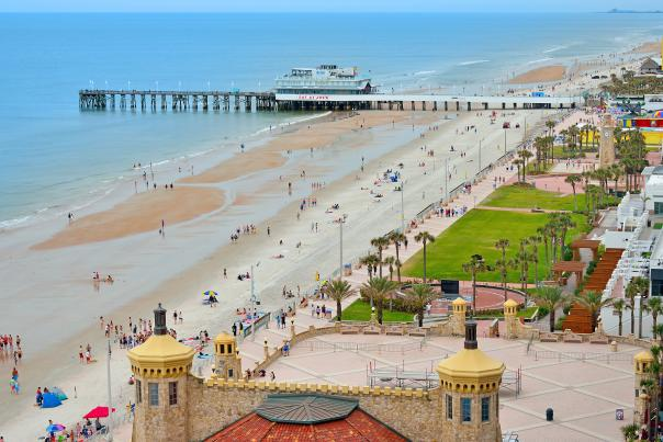 An aerial view of the wide Daytona Beach coastline and the Daytona Beach Pier and Oceanfront Bandshell