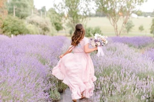 Woman running through lavender at Black & Blue Berry Farm
