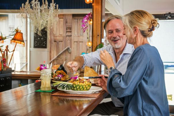 A couple enjoys a romantic dinner at Salt Fish Restaurant and Tiki Bar in Carolina Beach, NC