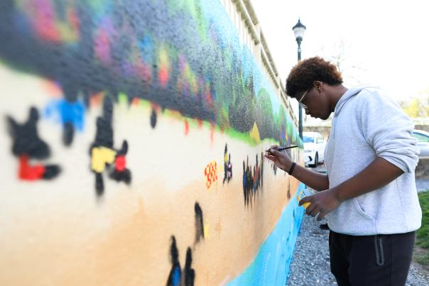 Students help pain the Carr's Beach Mural at MC3