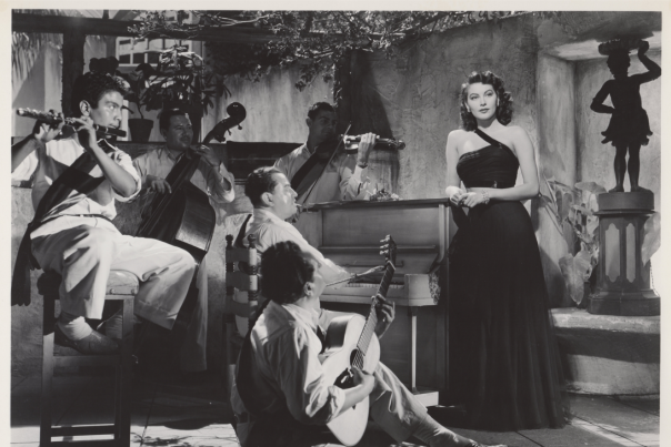 Scene from film The Bribe featuring Ava Gardner in one-shouldered black dress standing next to piano