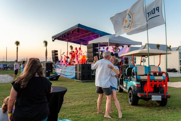 A couple dances in front of a music stage and next to a golf cart with Port Aransas flags