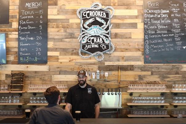 Bartender serves customer beer at Crooked Crab Brewery's bar