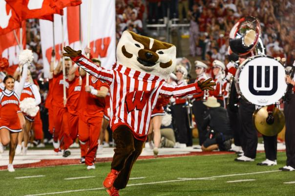 Bucky Badger runs onto the field at Camp Randall with his arms outstretched, with cheerleaders and the band behind him.