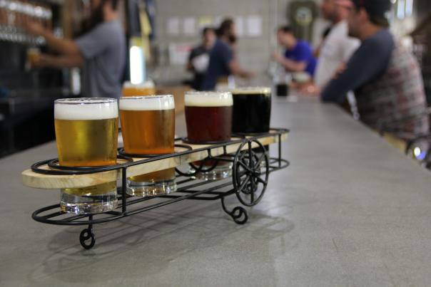 A flight of beer samples displayed apropros inwire-framed bi-plane-shaped holder at Crooked Can Brewing. Flight sits on bar with people in background.