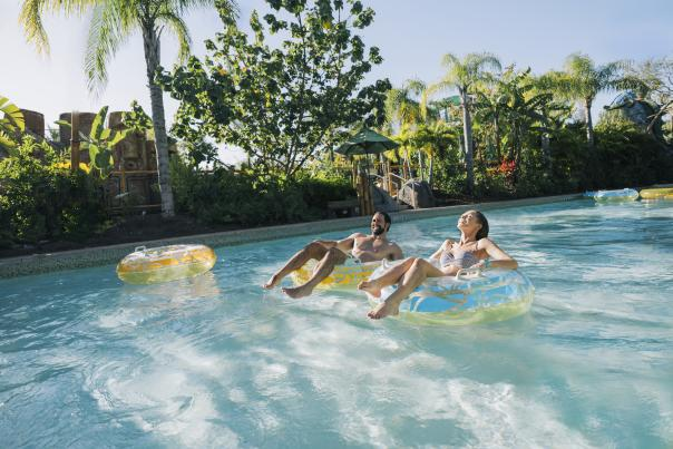 A couple floating in inner tubes on a lazy river in Universal's Volcano Bay.
