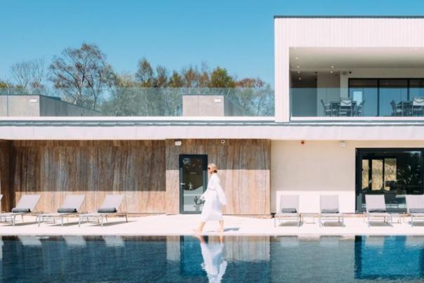 Woman in robe walking next to swimming pool at Silverlake Dorset