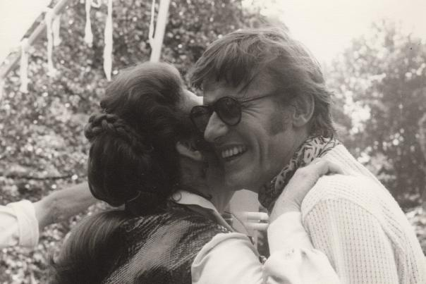 Ava Gardner embracing her friend Roddy McDowall as he smiles.