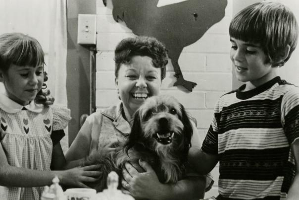 Black & White shot of Benji with boy, girl and woman