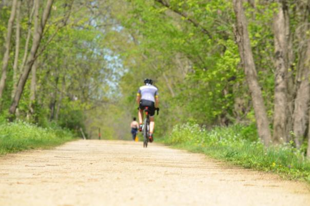 A biker rides on a gravel portion of the Military Ridge State Trail